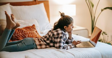 ethnic woman surfing internet on laptop on bed