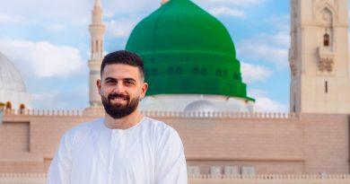 man in white long sleeve shirt standing near a mosque