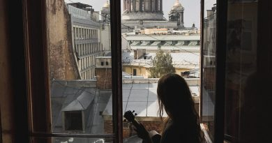 silhouette of a woman holding a ukulele sitting by the window looking at the city